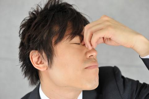 スマホで目が疲れている男性
