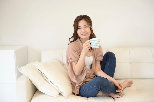 温かいドリンクを飲んでるソファに座った女性