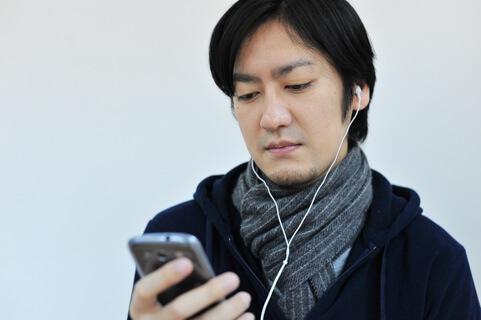 スマホを使って音楽を聴く男性