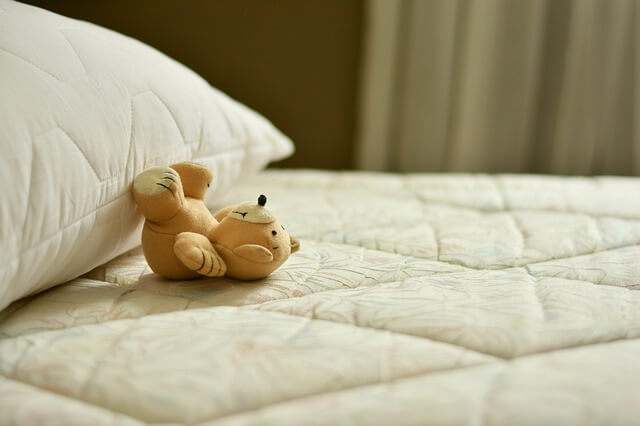 マットレスで寝転ぶクマのぬいぐるみ