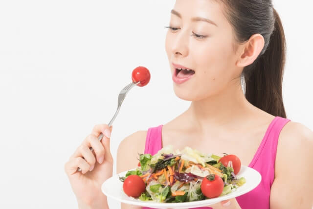 味わいながらサラダを食べている女の人