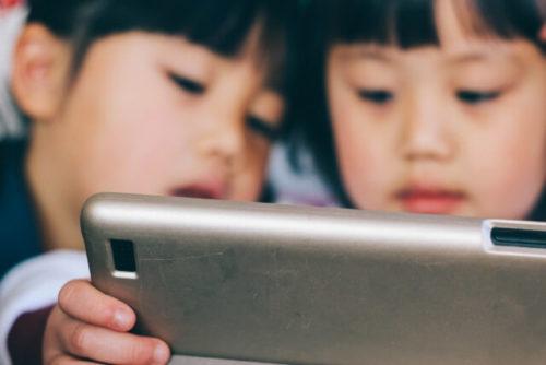 渋滞中に車内でタブレットを使ってアニメを観ている子供たち