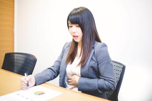 オフィスで就業中に小腹がすいてお腹の音がした女性