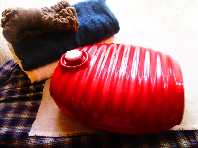 ベッドの上にある赤い湯たんぽと湯たんぽカバー