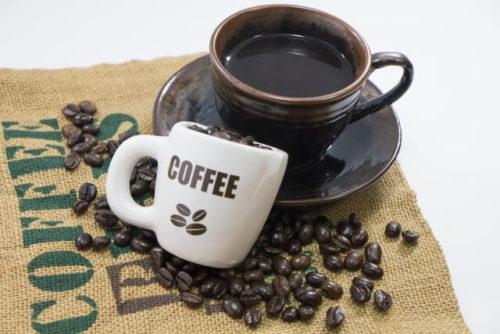 熟睡を防ぐコーヒーの入ったカップとコーヒー豆