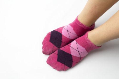 女性好みのかわいいピンク色の靴下を履いた人