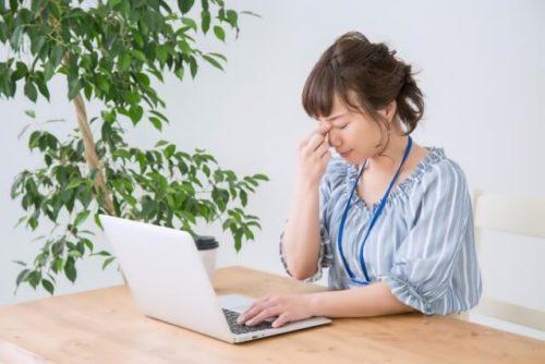 午前中の疲れが目に出てきた女性がデスクに座っている