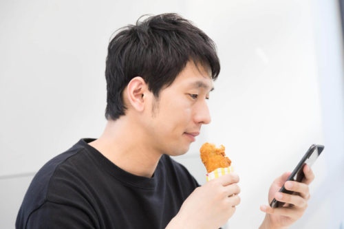 揚げ立てのフライドチキンを食べている男性