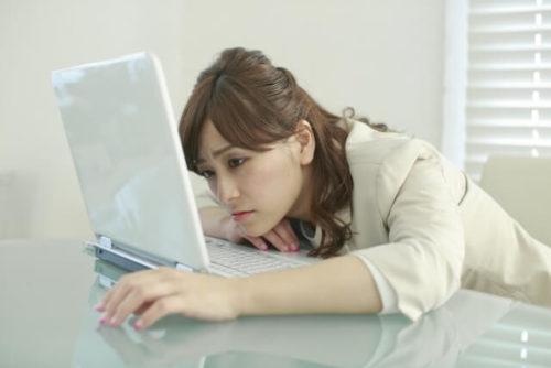 仕事のストレスで不安感が襲ってきているデスクワーク中の女性