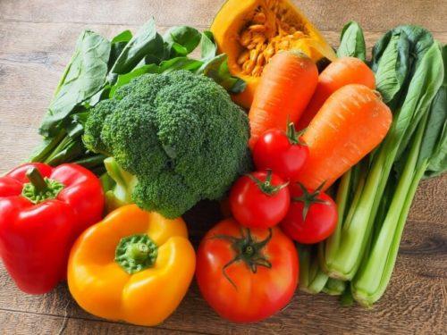 ブロッコリーやトマトなどたくさんの野菜が机に乗っている
