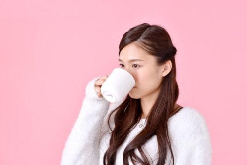 生姜湯を飲んで体を温めている女性