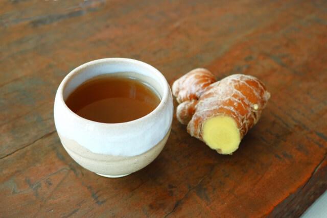 生姜湯の入った湯のみと生姜のかけらが机の上にある