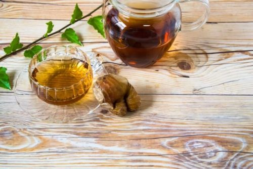 生姜紅茶の入ったティーポットとグラスが机の上にある