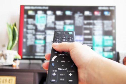 ソファで長時間テレビ鑑賞をしている人がリモコンを持っている