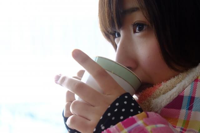 寒さ対策を考えながら温かいお茶を飲んでいる女性