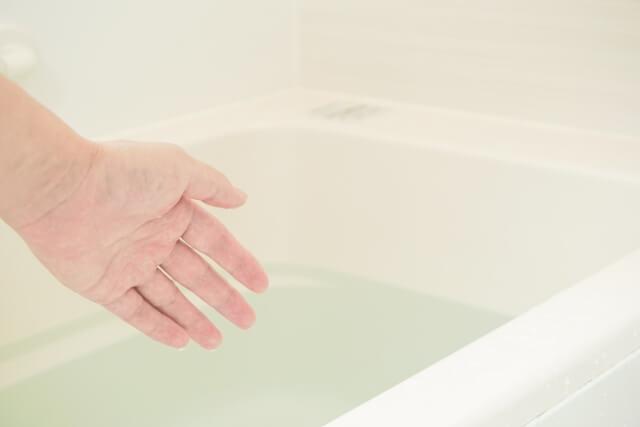 ヒートショックプロテインの効果を実感するために風呂の温度を触って確かめている人の手