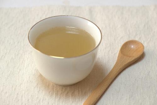 生姜湯の入った湯のみと混ぜるためのスプーン
