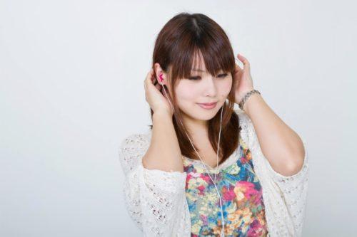 歯ぎしりを改善しようと癒し効果のある音楽をイヤホンで聴いている女性