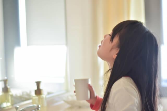 風邪予防にお茶でうがいをする女の子