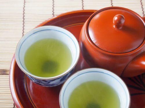 うがいに効果的な緑茶が入った湯のみが急須と一緒におぼんの上に2つある