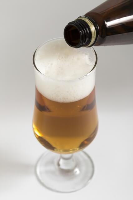 ビンビールをビールグラスに注いでいる