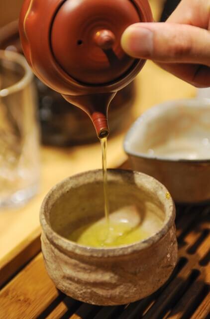 緑茶を急須で湯のみに淹れている