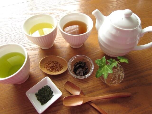 煎茶や緑茶やほうじ茶の入った湯のみと急須を机の上に置いている