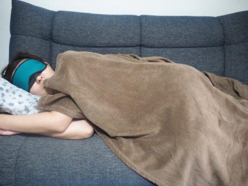 お酒を飲んでソファでうとうと寝ている人