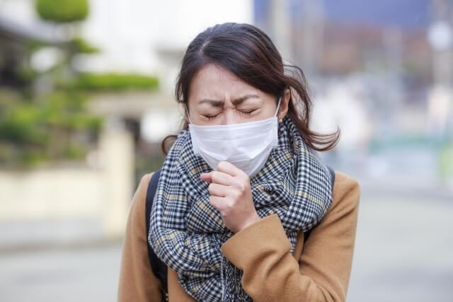 花粉症でくしゃみが出る女性が歩いている