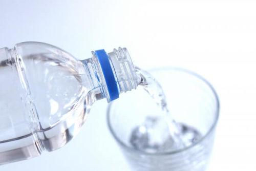 軟水の入っているペットボトルからお水をコップに注いでいる