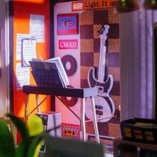 ミニチュアハウスの壁にギターなどの小物類がセットされている