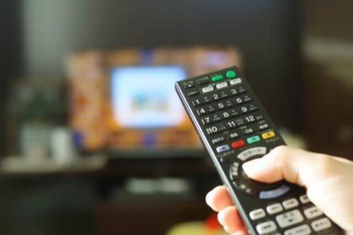 自宅のテレビにリモコンを剥けている人の手
