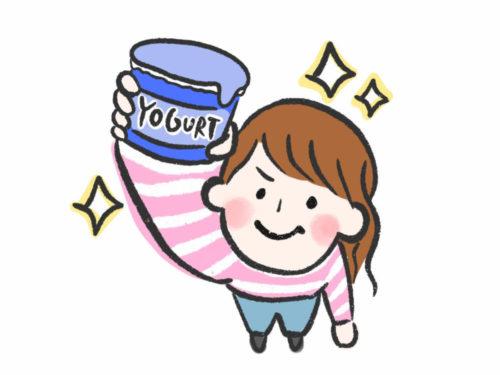 ヨーグルトのカップを手にもって掲げる女性