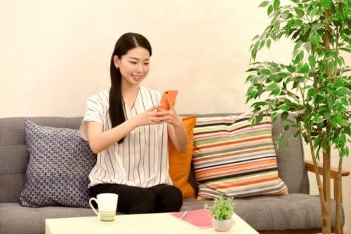 自宅のソファでオンラインショップで買い物をする女性