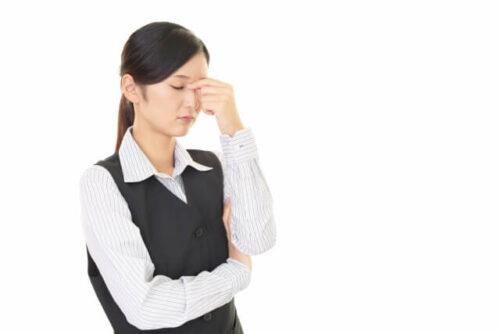 ストレスを感じて眉間に手を置く会社員の女性