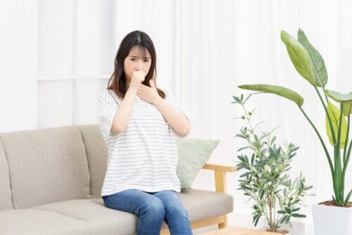 のどの不調を感じている女性がソファに座っている